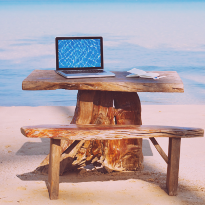 Picnic bench on the beach, made out of a tree, with a laptop on top. The laptop has an image of rippled water. The waves are in the distance.